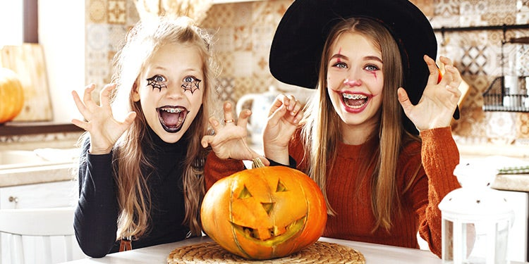 Two girls in costume with a pumpkin