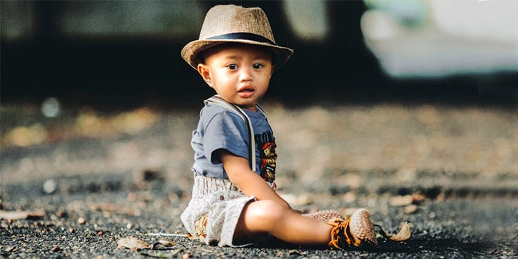 Infant sitting on the ground.